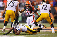 Fitzgerald Toussaint #33 of the Pittsburgh Steelers is tripped up while carrying the ball against the Cincinnati Bengals during the Wild Card playoff game at Paul Brown Stadium on January 9, 2016 in Cincinnati, Ohio. (Photo by Jared Wickerham/DKPittsburghSports)