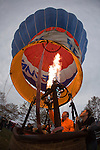 """A Remax hot air balloon pilot  at the 2008 Shenandoah Valley Hot Air Balloon Festival at Historic Long Branch in Millwood, Virginia fires a propane burner to heat the air in the balloon """"envelope"""" to keep the balloon upright.  Since hot air rises, this causes the balloon to stand up, and eventually fly."""
