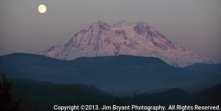 A full moon rises above Mt. Rainier. Rainier  is a heavily glaciated, dormant volcano surrounded by alpine parks. The 14,411 foot volcano which covers 228,480 acres was designated a National Park in 1899. Washington. Jim Bryant Photo. ©2013. All Rights Reserved.