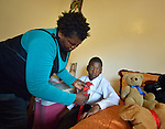 Tarisayi Zhanje helps her grandson, Hailey Kushaya, get ready for school in Harare, Zimbabwe. She cares for the 9 year old since his parents died. His appropriately-designed and fitted wheelchair was provided by the Jairos Jiri Association with support from CBM-US.