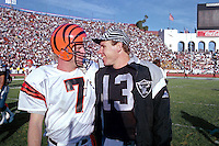 LOS ANGELES, CA - Quarterback Jay Schroeder of the Los Angeles Raiders, right, and quarterback Boomer Esiason of the Cincinnati Bengals talk after the Raiders won their AFC Playoff Game at the Los Angeles Memorial Coliseum in Los Angeles, California on January 13, 1991. Photo by Brad Mangin.