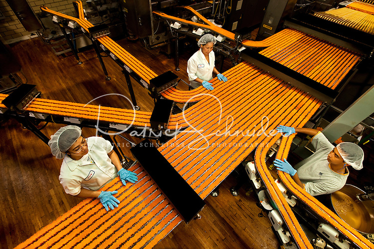"""Charlotte, NC-based Lance Inc., is one of the largest snack food manufacturers and distributors in the United States. The publicly traded manufacturing company makes snack crackers, sometimes referred to as """"Nabs."""" Photo shows the brightly colored orange ToastChee Crackers (peanut-butter-filled cheese crackers) moving through the manufacturing process. Lance Inc., products include sandwich crackers and cookies, potato chips, crackers, cookies, sugar wafers, nuts, restaurant-style crackers and candy."""