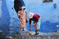 2 women, one sweeping the steps, in a street painted blue in the medina or old town of Chefchaouen in the Rif mountains of North West Morocco. Chefchaouen was founded in 1471 by Moulay Ali Ben Moussa Ben Rashid El Alami to house the muslims expelled from Andalusia. It is famous for its blue painted houses, originated by the Jewish community, and is listed by UNESCO under the Intangible Cultural Heritage of Humanity. Picture by Manuel Cohen