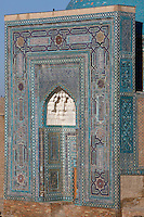 """Detail of portal of Mausoleum of the middle group, (""""Nameless 1"""" Mausoleum), 1380s, Shah-I Zindah ensemble, and in the distance the blue cupola of the Bibi-Khanym Madrasah and mausoleum, Samarkand, Uzbekistan, pictured on July 19, 2010, at dawn. The Shah-i-Zinda Complex is a necropolis of mausoleums whose legendary origin dates back to 676 when Kussam-ibn-Abbas arrived to convert the locals to Islam. So successful was he that he was assassinated whilst at prayer. His grave remains the centre of the sacred site which grew over many centuries, especially the 14th and 15th, into an architecturally stunning  example of ceramic art. The Mausoleum of the middle group.(""""Nameless 1"""" Mausoleum) was created by Usto Alim Nesefi, and is decorated  with relief painted majolica. The portal decorations are notable for the symbol of """"octagonal stars"""". Samarkand, a city on the Silk Road, founded as Afrosiab in the 7th century BC, is a meeting point for the world's cultures. Its most important development was in the Timurid period, 14th to 15th centuries. Picture by Manuel Cohen."""