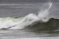 A wave, smoothed by slow shutter speed, gets the better of a surfer and his board.
