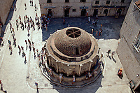 Aerial view of tourists in square with public fountain