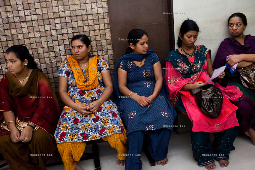 Patients, surrogates, and clients wait in the reception area in the Akanksha Infertility Clinic in the small town of Anand, Gujarat, India. .The Akanksha Infertility Clinic is known internationally for its surrogacy program and currently has over a hundred surrogate mothers pregnant in their environmentally controlled surrogate houses. .Photo by Suzanne Lee