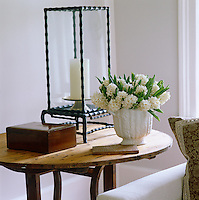 A detail of a vase of white hyacinths and a lantern on a wooden side table