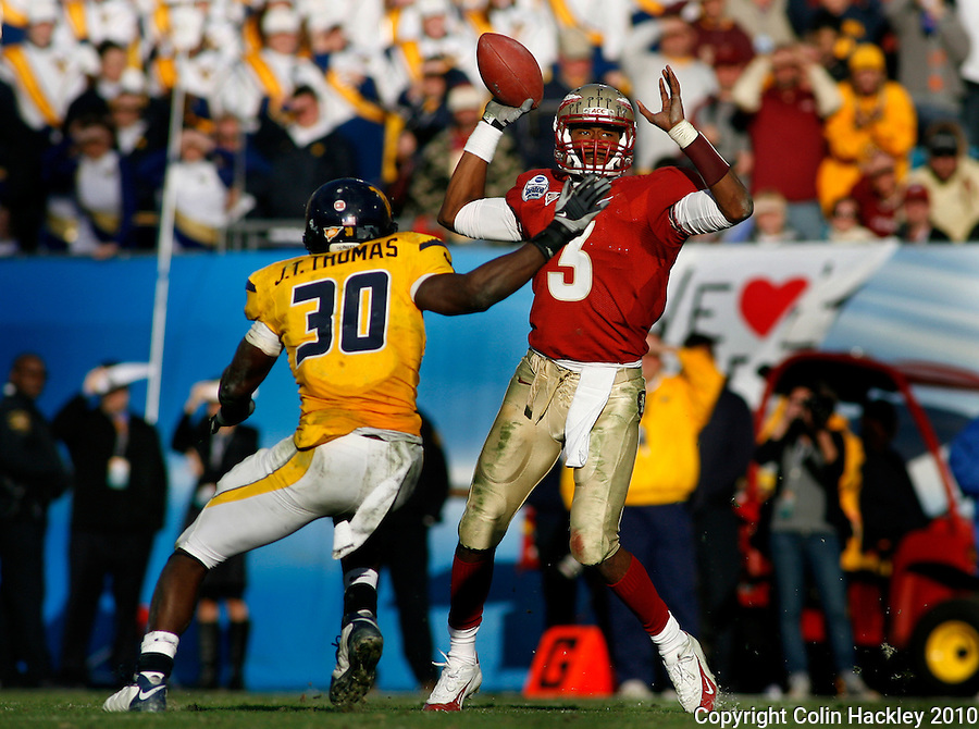 JACKSONVILLE, FL 1/1/10-FSU-WV FB CH67-Florida State's EJ Manuel throws against West Virginia as J.T. Thomas closes during second half Gator Bowl action Friday in Jacksonville, Fla. The Seminoles beat the Mountaineers 33-21..COLIN HACKLEY PHOTO