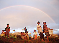 "April 15th, 2004-Ermera, Timor-Leste-A group of young children play in a graveyard near a small town in mountainous Ermera District known as ""Ponilala,"" as the setting sun and rain clouds work together to create golden light and rainbow.  Photograph by Daniel J. Groshong/Tayo Photo Group"