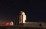 As the crossing gates lower, an eastbound train lights up the old grain elevator at Chana, IL under a starry night sky.