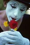 Mime performing at Seattle Center smelling flowers with white face and gloves Seattle Washington State USA