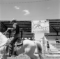 A cowboy enters the rodeo arena, Broadus, Mont.