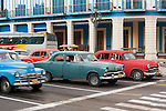 Havana, Cuba; classic American cars at an intersection along the Paseo de Marti during morning rush hour