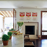 An Andy Warhol Campbell Soup Can print hangs above the fireplace in the open plan kitchen/dining area