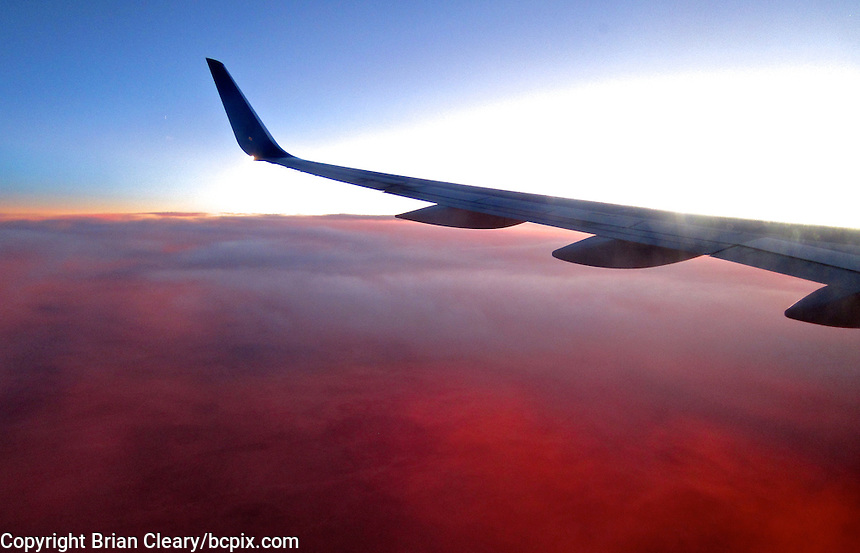 Red clouds at sunset looking out the airplane window, photographed with Canon Elph 300HS, November 30, 2011.   (Photo by Brian Cleary/www.bcpix.com)