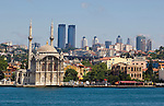Mosque at Ortakoy disrtrict on the Bosporus Sea with emeging modern skyline in background, Istanbul, turkey