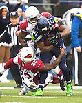 Seattle Seahawks running back Marshawn Lynch (25) is tackled by Arizona Cardinals linebacker Daryl Washington (58) and safety Tony Jefferson (22) during the 2nd quarter at CenturyLink Field in Seattle, Washington on December 22, 2013.   Lynch rushed for 71 yards on 18 carries in the Seahawks 10-17 loss to the Cardinals.  ©2013. Jim Bryant Photo. ALL RIGHTS RESERVED.