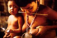 Yanomami indigenous people. Woman breast-feeds young monkey. Amazon rain forest, state: Roraima, Brazil.