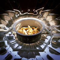 A pot of potatoes cooking without water on a solar cooker. The temperature of these cookers can reach 200 degrees Celsius. With the financial help of the Dutch Council for Refugees, a total of 6,300 solar cookers will be distributed amongst the Bhutanese refugees living in the region. The solar cookers consist of a reflective, aluminium, parabolic-shaped device that concentrates the sun's rays onto cooking pots placed on a frame in the centre of the dish. The dish has to be adjusted to the new position of the sun around every 10 minutes. It takes about 55 minutes to prepare a cooked meal on a sunny day and it is hoped that using the solar cookers will alleviate pressure on resources and reduce kerosene consumption by 75%...