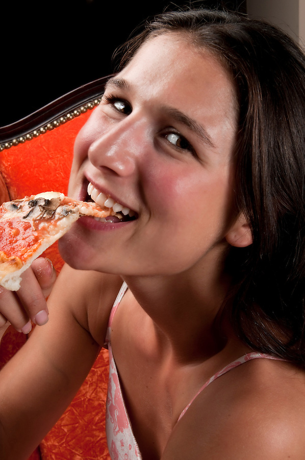 Young woman smiling and eating pizza very happy.