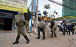 Cambodian police, carrying shields and batons, walk along the street in preparation for a demonstration in Phnom Penh..