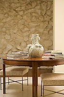 Detail of a ceramic vase on a round wooden table infront of an exposed stone wall