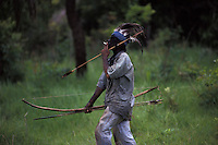 Brazil. Guarani-Kaiowas indigenous people. Acculturated brazilian indian smoking cigarettes and wearing clothes. Mix of traditional culture ( native weapons, like arrows ) and influence of the white culture.