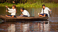 Schoolgirls in uniform paddle their way home in Kompong Khleang, one of the  floating fishing villages on Tonle Sap lake, Cambodia