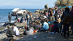 Refugees gather on a beach near Molyvos, on the Greek island of Lesbos, on October 29, 2015, after they crossed the Aegean Sea from Turkey in small overcrowded boats provided by Turkish traffickers to whom the refugees paid huge sums. They were received in Greece by local and international volunteers, then proceeded on their way toward western Europe.