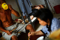 Textile workers eat and sleep in their dormitory at a garment factory. The factory, which specifically carries out a wear-and-tear process used to achieve a fashionable distressed look, produces approximately 10,000 pairs of jeans every day. Thousands of workers labour through the night scrubbing, spraying and tearing jeans in order to meet the production demand. China, the &quot;factory of the world&quot;, is now one of the world's largest producers of jeans and its textile workers are among the 200 million migrant labourers criss-crossing the country looking for a better life.