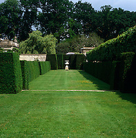 A classical stone urn is the focal point of this grass walkway lined with clipped hedges