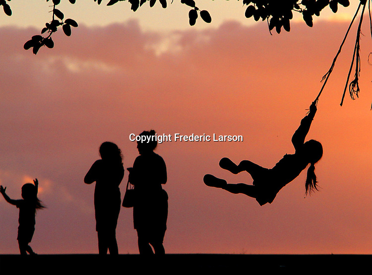 A young girl swings from a tree-vine while being silhouetted by the sunset on Magic Island, Honolulu, HI.