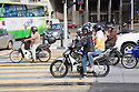 Mopeds and motorcycles at intersection. These vehicles are a common form of transportation in Malaysia. Kuala Lumpur, Selangor, Malaysia