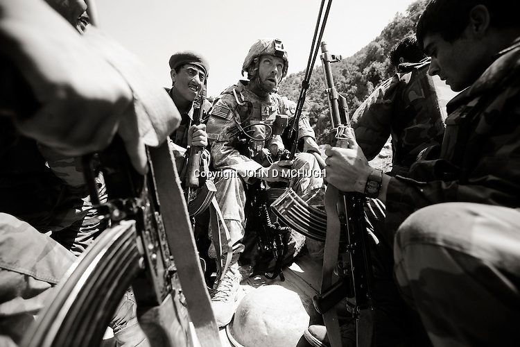 US Embedded Tactical Trainer (ETT) Master Sergeant Best, (C) rides in the back of a Ranger pick-up with soldiers from 1st Company, 2nd Kandak, 201st Corps, Afghan National Army (ANA) as they move to assist another ANA Company that had been ambushed near Kamu outpost in Nuristan Privince, north-east Afghanistan, 14 May 2007. Best's ANA/ETT unit and elements of White Platoon, Able Company, 3/71 Cav, 10th Mountain Division, were called upon to act as a Quick Reaction Force to the nearby ambush, and would get caught up in a major firefight soon after. By the end of the day there were 15 ANA dead, 4 wounded, and one believed captured by insurgents. 6 US personnel and 1 Irish photographer were also wounded during the fight. (John D McHugh)