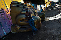 A Brazilian man rests on a damaged carnival sculpture outside the Samba school workshops in Rio de Janeiro, Brazil, 14 February 2012. Most of the large carnival floats, colorful designs and fancy costumes are dismantled, cut into pieces or simply thrown into garbage right after the last day of the Carnival. The low-tech materials as fiberglass, plastic or polystyrene, which most of the of the carnival floats and statues are made of, are stocked in the warehouses to be recycled and used in the future parades. However, there is no use for some of the statues so they slowly fall apart into pieces forming a ?Carnival cemetery? in the industrial yards around the port of Rio de Janeiro.
