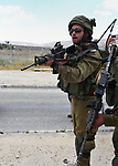 An Israeli soldier aims his weapon at palestinian protesters during a demonstration in support of prisoners refusing food in Israeli jails at the Hawara checkpoint, south of Nablus in the Israeli-occupied West Bank, on May 23, 2017, during a visit of the US president to Israel and the Palestinian territories. A general strike in support of Palestinian hunger strikers in Israeli prisons, coincided with Trump's arrival in Israel and the Palestinian territories. Photo by Ayman Ameen