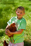 Quincy Shern, 9 holds a chicken near the coop at Featherdown Farm at the Chaffen Family Orchards near Oroville CA, Saturday April 20, 2013. She was there with her family from Chico CA.<br /> Brian Baer/Special to the Bee