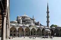 Low angle view of cascading domes and arcade (revak) surrounding the courtyard with hexagonal fountain, and a minaret to the right of the image, Sultan Ahmed Mosque, or Blue Mosque, 1609-16, by Mehmet Aga, Istanbul, Turkey. The Sultan Ahmed Mosque, commissioned by Sultan Ahmed I, dominates the Istanbul skyline with its cascading domes and six minarets. Built near the Hagia Sophia, it combines Byzantine style with Islamic architecture. The court, surrounded by a continuous vaulted arcade (revak), is about as large as the mosque itself. The historical areas of the city were declared a UNESCO World Heritage Site in 1985. Picture by Manuel Cohen.