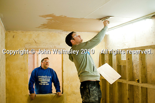Plastering student usin g a trowel to apply fresh plaster overhead, Able Skills, Dartford, Kent.