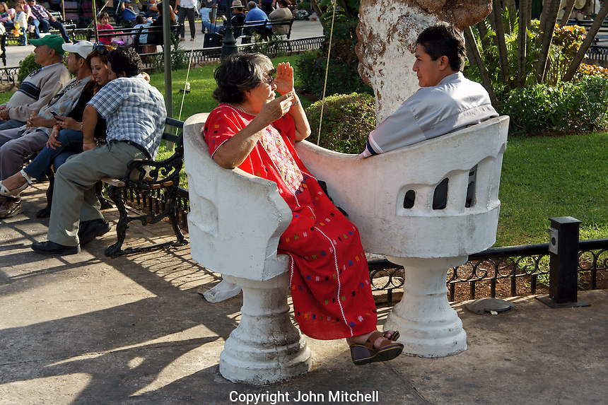 Elderly woman and younger man sitting and chatting in love seats in the main square of Merida, Yucatan, Mexico