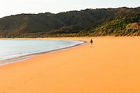 Woman enjoying sunrise on golden beach in Totaranui, Abel Tasman National Park, Nelson Region, New Zealand