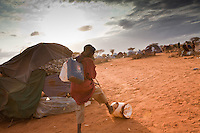 A Somali girl collecting water for her family in the desert at the edge of Ifo camp near Dadaab, Kenya. These settlements are unlit and lacking security. The duty of fetching water falls to girls culturally and they are at risk of being attacked and raped. 1300 refugees are arriving every day from Somalia where they have fled drought and civil war.