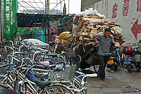 Man pulling a large cart full of carton, Datong, Shanxi, China.