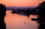 Silhouetted rower on Montlake Cut sunrise opening day of boating with boats moored