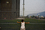 A ticketless girl watches the venues of the Olympic Games from a security fence in Beijing, China on Monday, August 4, 2008. The city of Beijing is gearing up for the opening ceremonies of the Olympic Games.  Kevin German