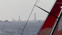 FRANCE,  Point Penmarc'h. 1st July 2012. Volvo Ocean Race, Leg 9 Lorient-Galway.  Phare d'Eckmuhl, ( also known as Point Penmarc'h Light or Saint-Pierre Light ) through the rigging of CAMPER with Emirates Team New Zealand.