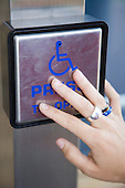 Woman's hand on a disability access door button. MR