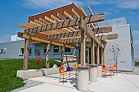 Outdoor art and sitting area under a recycled wood arbor at Fifth Town Artisan Cheese Co's LEED certified state of the art facility in Prince Edward County, Ontario.
