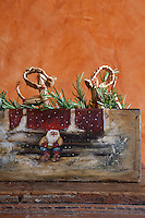 Detail of a hand-painted wooden Christmas trough filled with sprigs of fresh rosemary and straw animals